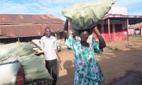 Ajulongo Ruth receives a bag of cassava cuttings to replant her garden